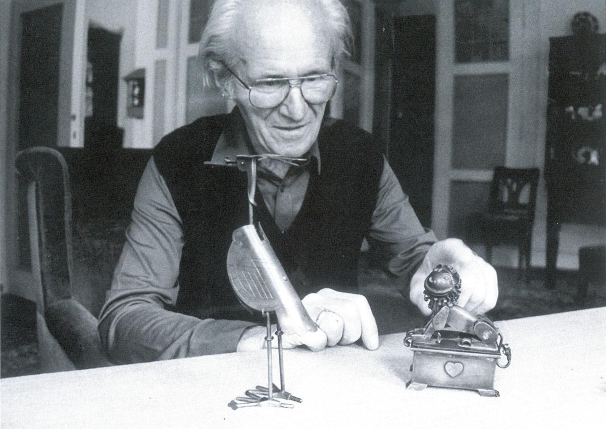 Hans Happ mit Briefwaage und Patience-Kastchen aus Metall